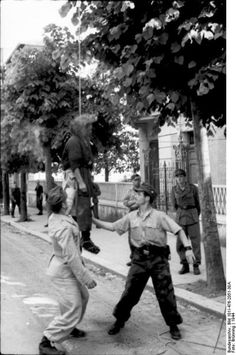 German soldiers have just barbarically hanged a woman from a tree in Rome, Italy, and are stopping her from swinging (1944).