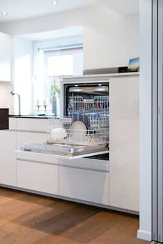 A custom high dishwasher makes clearing it out and filling it much easier. This built-in dishwasher fits perfect into the white and minimalism kitchen.