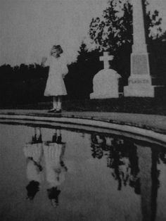 Photograph, taken in 1925 of a girl visiting the grave of her twin sister who died in a house fire the year before. Parents of the girl saw her, on many occasions, talking to her sister like she was playing in her room, but no one was there, and they thought it was just part of the grieving process.