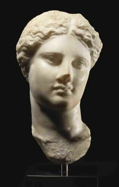 A GREEK MARBLE HEAD OF ISIS-APHRODITE  HELLENISTIC PERIOD, CIRCA 3RD CENTURY B.C.  Probably from Alexandria, finely sculpted, her head slightly turned to her left with downward gaze, long neck with naturalistic contours, bowed lips, her wavy hair centrally parted and pulled back, circular mortise on the crown, the reverse roughly hewn 9 in. (22.8 cm.) high