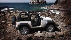 white jeep wrangler on the shore <3
