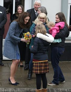 Catherine, Duchess of Cambridge accepts a bunch of posies from a group of schoolchildren who came down to say hello as she arrives to officially open the new EACH charity shop on March 18, 2016 in Holt, United Kingdom.