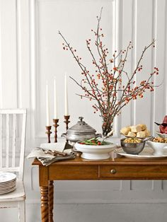 "Free up prime dinner-table real estate by moving oversize arrangements to the buffet. And don't bother with elaborate floral fantasies: Just go ""shopping"" in your backyard for branches of holly, crab apple, or bittersweet berries. Then bring in-demand items — butter, gravy, cranberry sauce — to the middle of the table. Add this centerpiece to  you're Thanksgiving table."