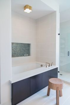 Shower tile wraps the corner and flows into the area around the tub too, making for a more seamless look. Carla Aston Designer, Tori Aston Photographer