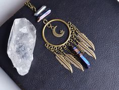 A gorgeous moon inspired piece decorated with feathers and crystals. This dangle piece will look great on a longer chain with a bohemian inspired