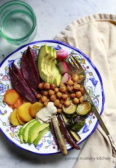 vegan nourish bowl with chickpeas -  Curried chickpeas with roasted Brussels sprouts, purple carrots, purple sweet potatoes, golden beets, and radishes, avocado, and tahini over a bed of quinoa.