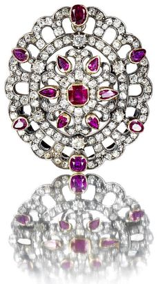 A diamond and ruby brooch/pendant, circa 1880 The central flower motif composed of collet-set cushion and pear-shaped rubies and old brilliant-cut diamonds, within a scalloped frame of further old brilliant-cut diamonds with oval and pear-shaped rubies set at intervals, mounted in silver and gold, diamonds approximately 3.70 carats total, French import marks, length 4.0cm