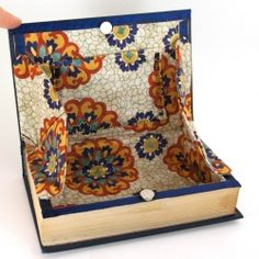 This is apparently a clutch...but wouldn't it make a great jewelry box?  A cutout book lined with fabric