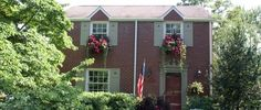 moss green on red brick w/shutters and window boxes