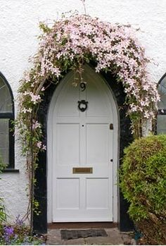 .Clematis growing over doorway arch. Photo by Mark Bolton.....I love the clematis flowers for that lady-like hat. Spring is on it's way.