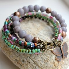 Multi strand bracelet with five strands of glass and stone beads in varying shades of sage green coffee mauve and purple onto memory wire