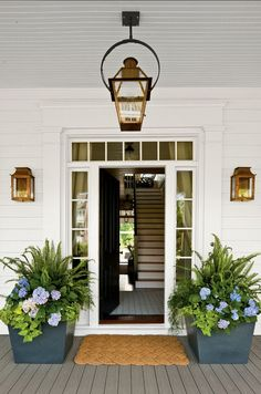 "Front Door Design Ideas. Beautiful front door, lighting and planters design. #Frontdoor #FrontEntry #Entry A perfect front entry! Exterior Lighting: Wall lanterns are the ""Williamsburg 16″ Flush Mount in Natural Gas by ""Bevolo"". Hanging lantern is the ""French Quarter 21″ on Yoke Brachet in Eletric, also from ""Bevolo"". Door mat is the Braided Coir Doormat, Double Wide, from Restoration Hardware."