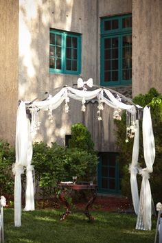 Our arbor.  8 yards of fabric from Hobby Lobby, cut in half and zip-tied in place.  Rose streamers hung at varying heights.  Home-made bow with pendant brooch in the center.  Tulle bows tied to each post a gather of fabric.