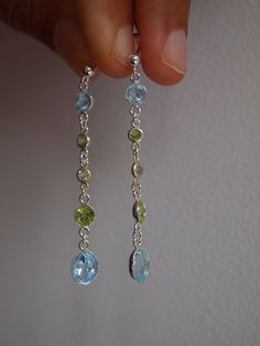 Beautiful genuine blue topaz, white topaz and green peridot drop earrings hand set in sterling silver and pure silver bezels using special jewellery glue by me. Absolutely beautiful pair of earrings, very classy, unique and elegant! Handmade and designed by ZahidasJewellery #blue topaz and peridot drop earrings #gemstone drop earrings sterling silver #peridot stone jewelry sterling silver #peridot stone jewelry #gemstone jewelry earrings ideas Peridot Earrings, Dangly Earrings, Sterling Silver Earrings Studs, Gemstone Earrings, Peridot Jewelry, Cluster Earrings, Drop Earrings, Unique Earrings, Blue Gemstones