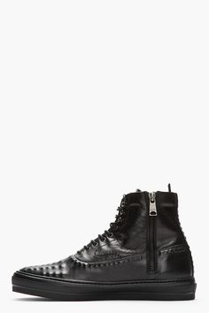 ALEXANDER MCQUEEN //  Buffed black leather covered stud sneakers  32259M050004  Ankle-high buffed leather sneakers in black. Covered stud accents throughout vamp, heel, and trimming lower upper. Round toe. Oxford-style tonal lace-up closure with three lace hooks at collar. Zip closure at interior face. Pull loop at heel collar. Tonal stitching. Tonal rubber sole. Upper and lining: leather. Sole: synthetic. Made in Italy.  $820 CAD