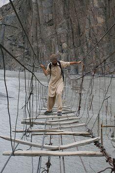A man crossing Wooden bridge in Northern  Pakistan