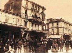 ΦΑΡΜΑΚΕΙΟ ΠΕΤΡΟΥ ΜΠΑΚΑΚΟΥ ΟΜΟΝΟΙΑ ΑΘΗΝΑ 1928  ΕΠΙΣΚΕΨΗ ΤΩΝ ΜΕΛΩΝ ΤΗΣ ΑΜΕΡΙΚΑΝΙΚΗΣ ΟΜΟΓΕΝΕΙΑΚΗΣ ΟΡΓΑΝΩΣΗΣ ΑΧΕΠΑ (AHEPA) ΣΤΗΝ ΑΘΗΝΑ. ΜΕΛΗ ΤΟΥ ΣΥΛΛΟΓΟΥ ΕΞΩ ΑΠΟ TΟ ΚΤΗΡΙΟ ΟΠΟΥ ΣΤΕΓΑΖΕΤΑΙ ΤΟ ΠΡΑΚΤΟΡΕΙΟ Ο ΦΑΡΟΣ ΚΑΙ ΤΟ ΦΑΡΜΑΚΕΙΟ ΤΟΥ ΜΠΑΚΑΚΟΥ. ΠΛΗΘΟΣ ΠΕΡΑΣΤΙΚΩΝ ΣΤΗΝ ΠΛΑΤΕΙΑ ΟΜΟΝΟΙΑΣ, ΠΡΟΣ ΤΗΝ ΠΛΕΥΡΑ ΤΗΣ ΟΔΟΥ ΑΓΙΟΥ ΚΩΝΣΤΑΝΤΙΝΟΥ. ΔΙΑΚΡΙΝΕΤΑΙ ΣΤΟ ΚΤΗΡΙΟ Η ΕΠΙΓΡΑΦΗ ΟΜΟΓΕΝΕΙΣ ΑΧΕΠΑΝΣ ΚΑΛΩΣ ΗΛΘΑΤΕ.  ΨΗΦΙΑΚΟ ΑΡΧΕΙΟ ΕΡΤ Συλλογή ΠΕΤΡΟΥ ΠΟΥΛΙΔΗ