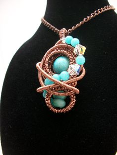 Wire wrapped pendant featuring turquoise and amazonite beads in antique copper finish. Pendant measures 1 x 2 and is accented with Swarovski crystals. Chain is 16 adjustable to 19 and secures with a lobster clasp.