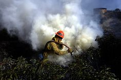 UP IN SMOKE: A firefighter fought a wild fire near Point Mugu State Park in California Friday. What started as a brushfire along the 101 freeway northwest of Los Angeles Thursday morning swelled to more than 6,500 acres by late afternoon, chasing thousands of residents from their homes. (Michael Nelson/European Pressphoto Agency)