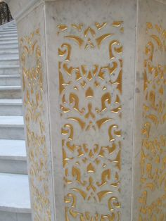The incised white marble covering the base of the handrail at the grand staircase.