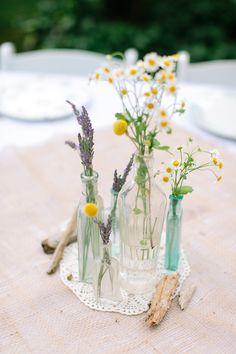 glass bottles with wild flowers  http://www.weddingchicks.com/2013/12/10/cape-cod-beach-wedding/