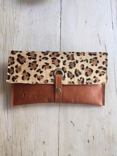 This leopard printed clutch is a perfect accessory to bring an edgy twist to a basic outfit. Its size is really practical: you can fit in your cell phone, your make-up, a small purse, your keys… Hand made with real foal fur front stamped in shades of black and brown leopard pattern. The