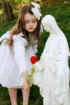 I'm not sure that this girl is actually a flower girl, but she looks one to me, so that's why I put this under wedding photography ideas. If I have a flower girl, I'd like to take a picture of her honoring Mary with a flower.