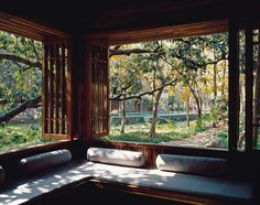 5.	The corner of the veranda accommodates a built-in sofa. From here, a swimming pool can be glimpsed through the trees