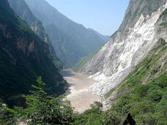 About 100 kilometers (62 miles) northwest of Lijiang Old Town lying between Jade Dragon Snow Mountain and Haba Snow Mountain is Tiger Leaping Gorge ((hu tiao xia)), which is believed to be one of the deepest gorges in the world. From the top of the gorge you look down the steeply angled (70-90 degrees) mountain sides to the rushing Golden Sands (Jingsha) River with its 18 frothing rapids more than 200 meters (about 700 feet) below. Tiger Leaping Gorge
