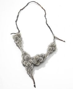 Sam-Tho Duong works with silver in conjunction with sweet water pearls. Using large numbers of small pearls he creates a lavish structure, a skin which also alludes to organisms. His jewellery has an almost classic, restrained feel.