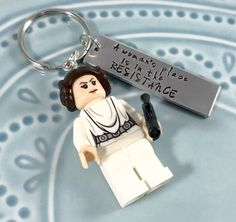 This awesome keychain was inspired by the A womans place is in the resistance imagery. Its perfect for anyone resisting the culture that exists in our current political system or generally smashing the patriarchy. I hand make both the lego Leia figure and the aluminum rectangle that is hand-stamped with the quote. The heavy duty metal rectangle is approximately 1/2 wide and 1 3/4 long. The lego arms and legs are moveable. Keychain is very durable and will stand up to regular use.  I...
