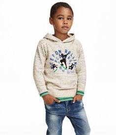 Een fijngebreide trui van zacht katoenen garen. De trui heeft een capuchon en een ribgebreide boord aan de onderkant en onder aan de mouwen.