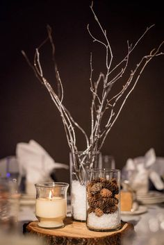 Faux snow winter wedding centerpieces with log slices, twigs, candles, and pine cones l MyHotelWedding.com