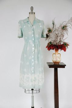 Vintage late 1930s dress is lovely in the pales possible aqua hue. Summerweight, this rayon and linen blend number has a lovely coarse-but-light texture with wonderful drape, and is perfect for sunny days. The pale, faded aqua is printed white pansy blooms scattered throughout, and large, detailed flowers along the hem and sleeves. The short sleeves are pleated to puff softly. The bodice offers a simple collar and two chest pockets. The pockets are accented with heavy shell buttons that…