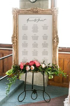 What a GORGEOUS table seating chart for a wedding.  I love that large gold frame with flowers. Photo by Union Eleven.
