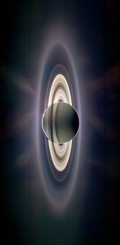 Saturn eclipsing the sun, with the Earth visible in the upper left section of Saturn's rings