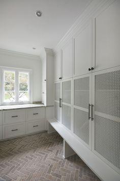 mudroom with mesh panel in cabinet doors, brick herringbone floor