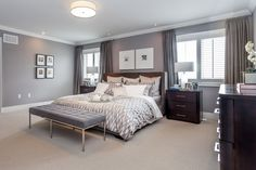 """This is a simple modern bedroom with a pleasing combination of colors, creating a timeless appeal and a gender-neutral look. Floors are carpeted in a light beige color, while walls are painted in light gray."""