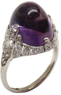 Art Deco amethyst and diamond ring, circa 1925. A large, oval cut cabochon amethyst set within a tapered frame set with rose and cushion cut diamonds, mounted in platinum. Via Diamonds in the Library.