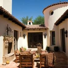courtyard. mediterranean/ spanish courtyard, open fireplace, table chairs, gravel, yet so charming.