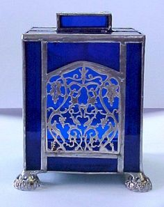 stained glass and silver tzedakah (charity) box