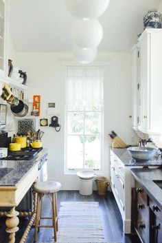 varied furniture, same countertop, hanging pans, wall, things on the floor, paper lanterns, stool   kitchen