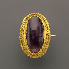 Roman Gold Brooch                                                                                                                                                        Culture :                  Roman                                              Period : Roman, 3rd century A.D.                                          Material : Gold and Amethyst
