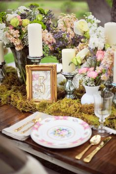European Vintage Inspired Wedding.  A base of moss for the table centerpieces. Chunky silver candlesticks and romantic English garden style floral arrangements.