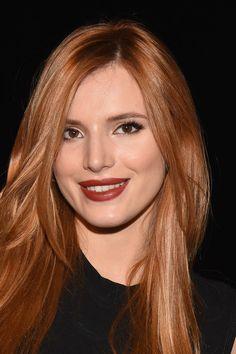 cheveux roux, robe noire sans manches, maquillage avec eye liner noir et  rouge à