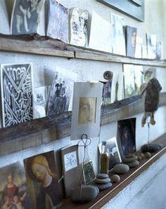 Display shelving using natural elements like rough cut wood and river rock. Photo display or inspiration board using natural elements.
