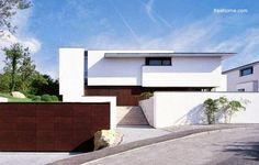 Fachada blanca de una residencia de dos plantas en desnivel estilo Minimalista