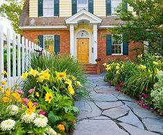 Create Cottage Appeal....Enlarged planting beds along a walkway bring color to a home's entrance. Here, a bluestone path lined with day lilies, zinnias, and coreopsis creates a warm invitation to the front door.