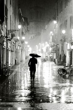 """""""On the late afternoon streets, everyone hurries along, going about their own business. Who is the person walking in front of you on the rain-drenched sidewalk? He is covered with an umbrella, and all you can see is a dark coat and the shoes striking the puddles.""""~Vera Nazarian"""