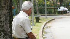 Idoso sentado no banco em um parque